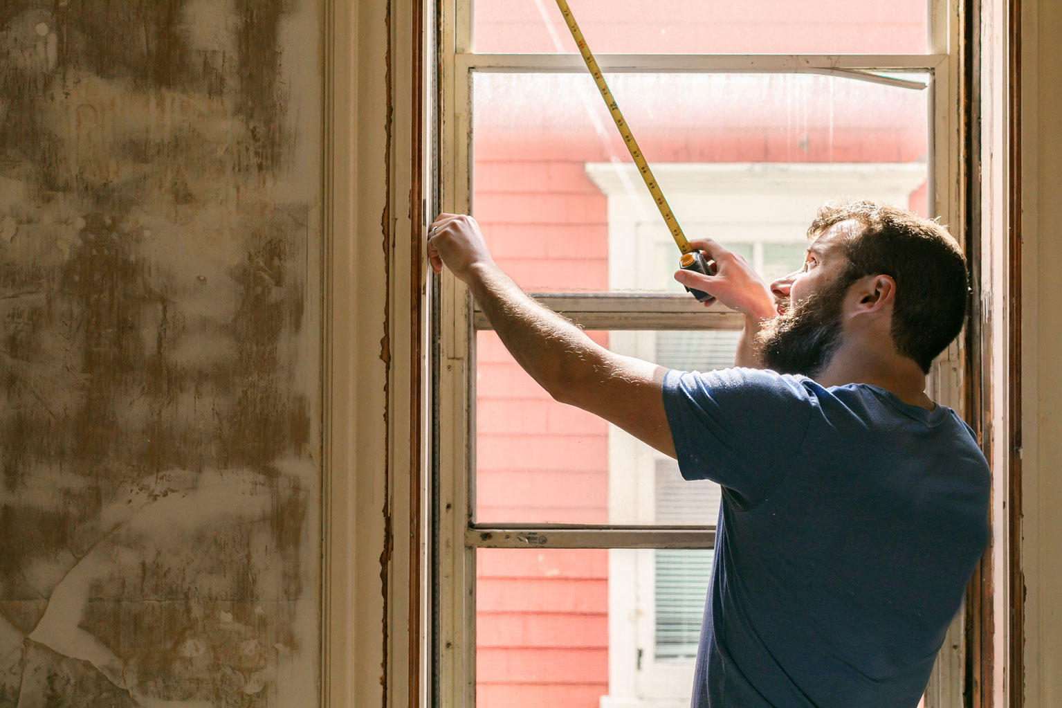 Construction worker holding measuring tape against energy efficient window