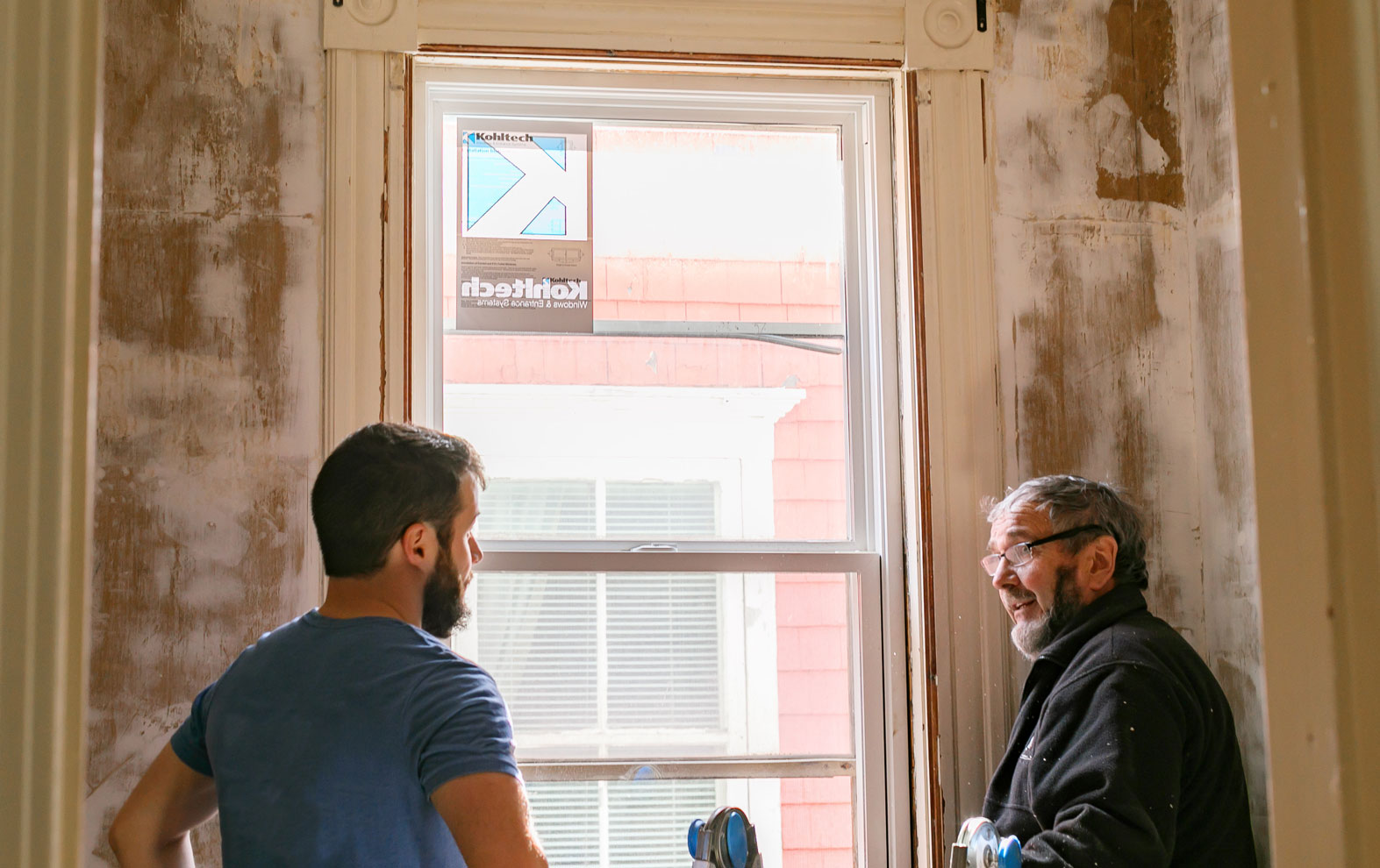 Construction works engaging in conversation while installing energy efficient windows